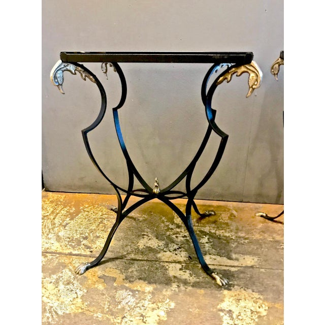 This is a superb pair of early 20th century French forged iron side tables detailed with cast brass phoenix finials and...