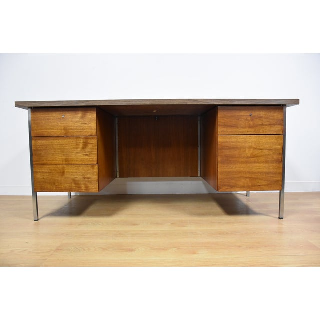 Offered is a mid century modern era walnut and chrome office desk with a formica top. This piece was manufactured by Knoll.