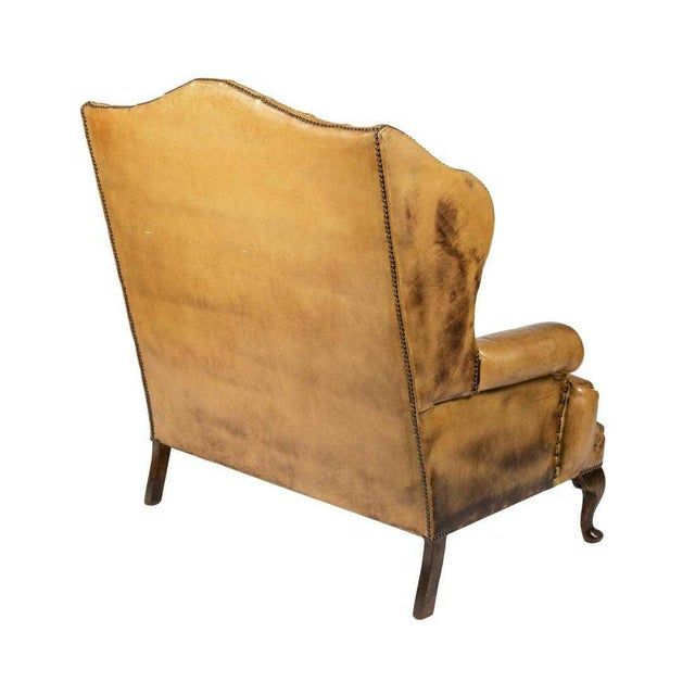 Tufted leather wingback loveseat in the style of Chippendale. Has a high back, wood legs, nice grain and patina to the...