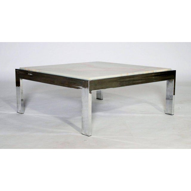 Large square polished chrome steel frame cocktail table with a removable white and gold marble top.