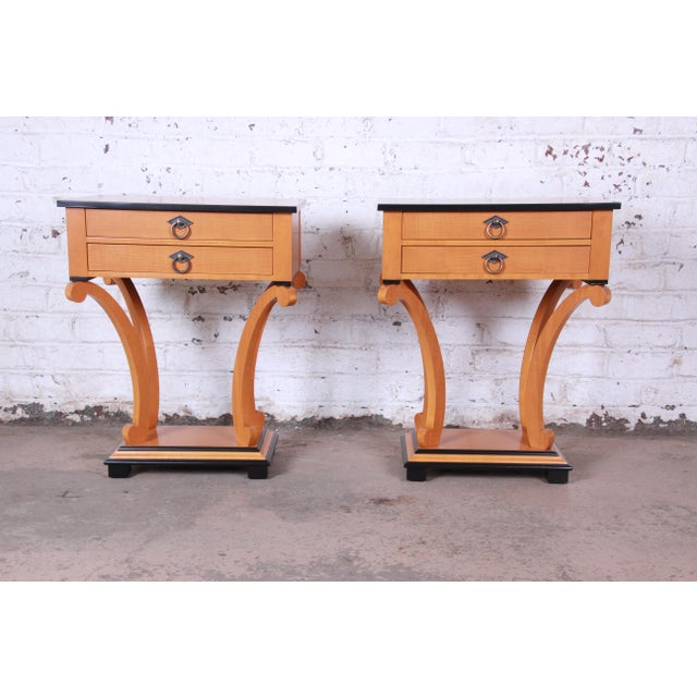 An exceptional pair of Biedermeier style nightstands or side tables by Baker Furniture. The nightstands feature stunning...