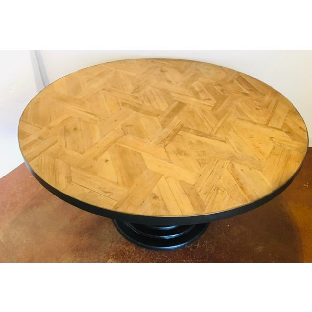 Stylish organic modern reclaimed wood round dining table, black wood base topped with a warm oak finished top, showroom...