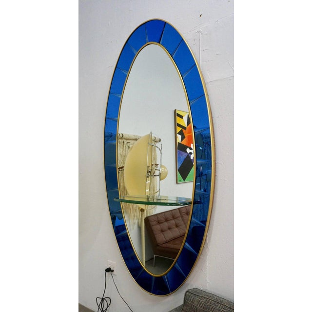 Beautiful large oval mirror, manufactured by Crystal Arte, Turin, Italy. The mirror is surrounded by beveled cobalt blue...