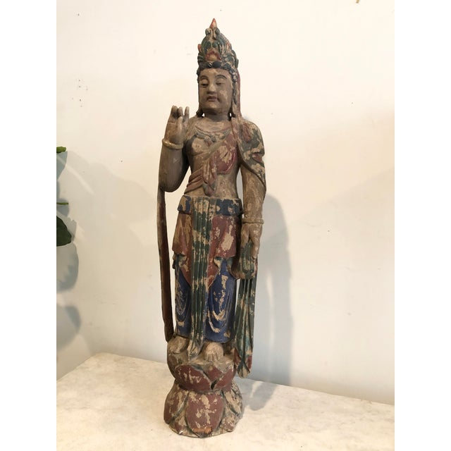Guanyin Bodhissatva, the Goddess of Mercy, depicted here in this Buddhist carved wood statue, stands atop a lotus flower...