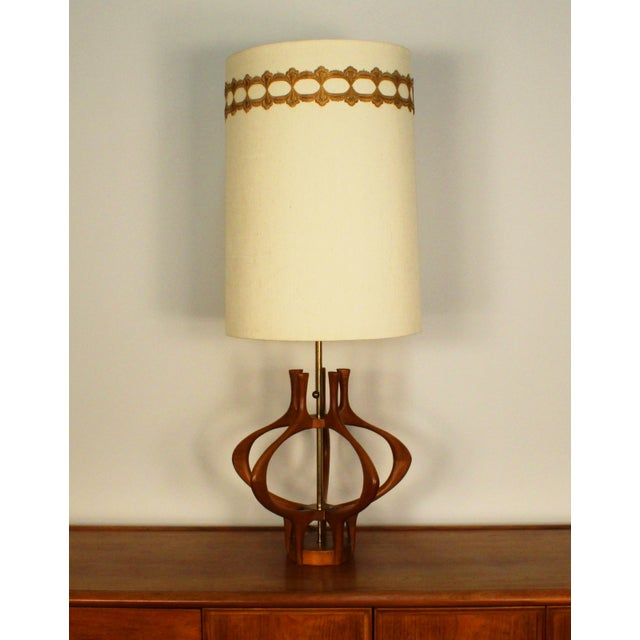 Elegant and organic wood sculptural mid-century table lamp with brass post by Modeline. Retains the original paper...