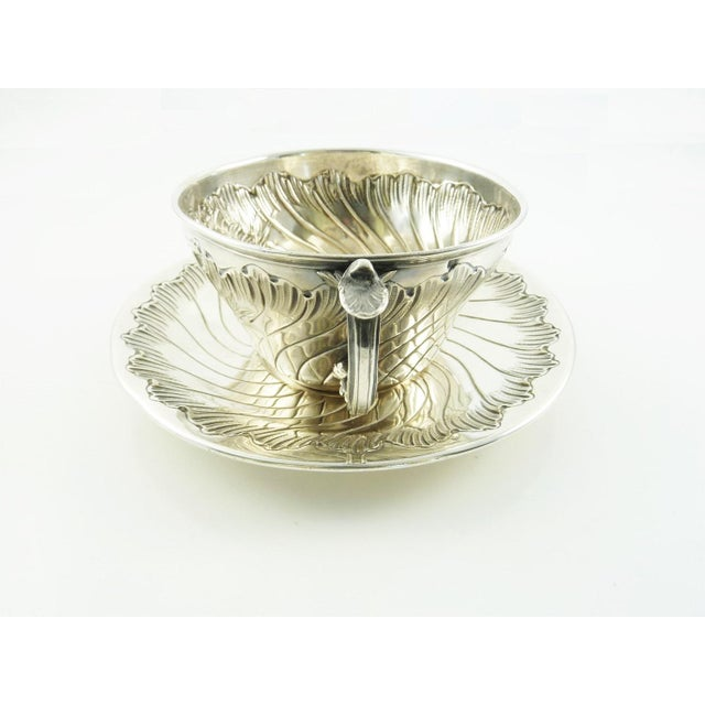 An impressive antique French sterling silver cup and saucer decorated in the Rococo manner. Delicate shells decorate the...