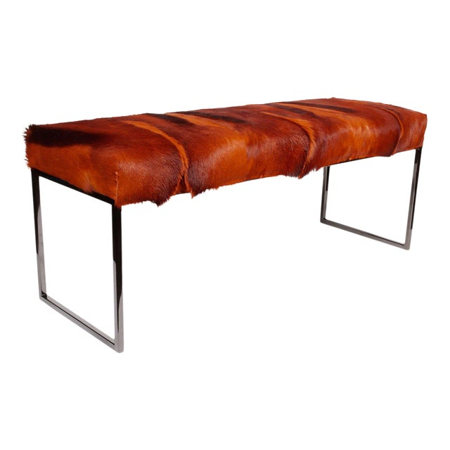 Exotic African springbok bench in hues of burnt orange. Mid-century modern style design with streamline base in black...