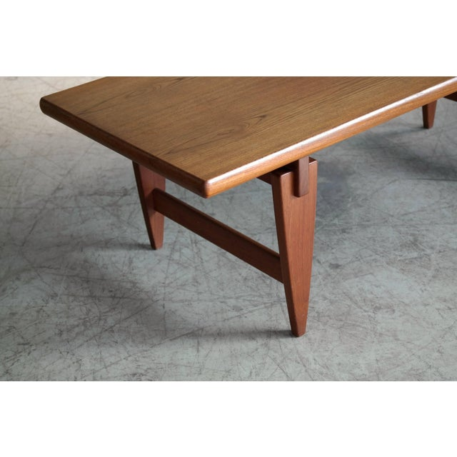 Beautiful coffee table by Illum Wikkelsø with distinctive triangular legs and floating top. Made in 1960s with a teak...