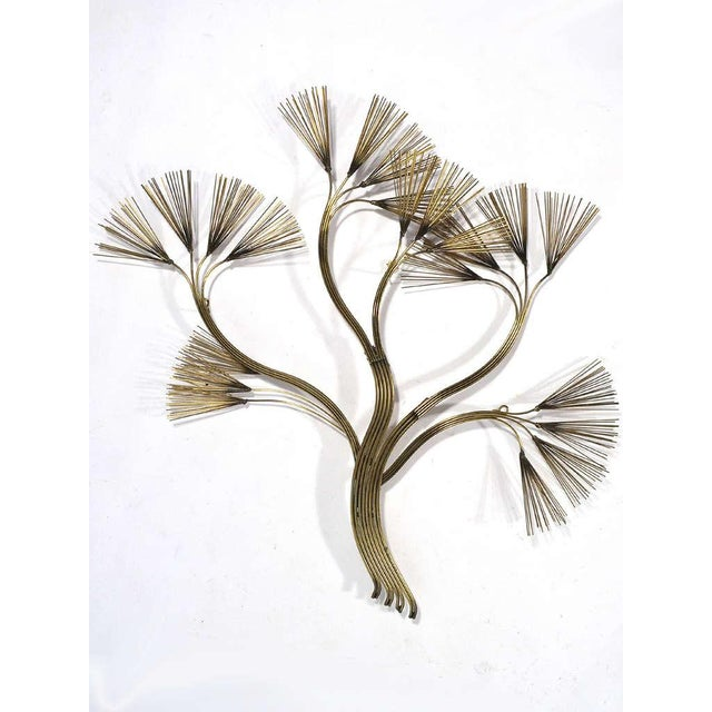 A fluid, organic wall sculpture in the form of a stylized plant form rendered in brass by Jere. Signed and dated.