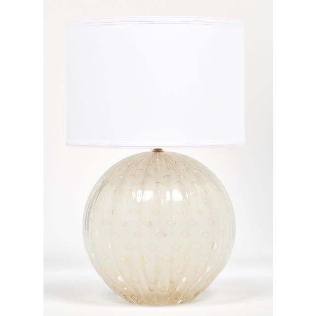 "Single hand-blown globe lamp made of Murano glass using the ""pulegoso"" technique. The glass has 23-karat gold leaf flecks..."