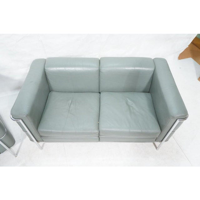 Chrome and teal leather loveseat and matching club chair by Jack Cartwright. In the manner of Le Corbusier LC2 line from...
