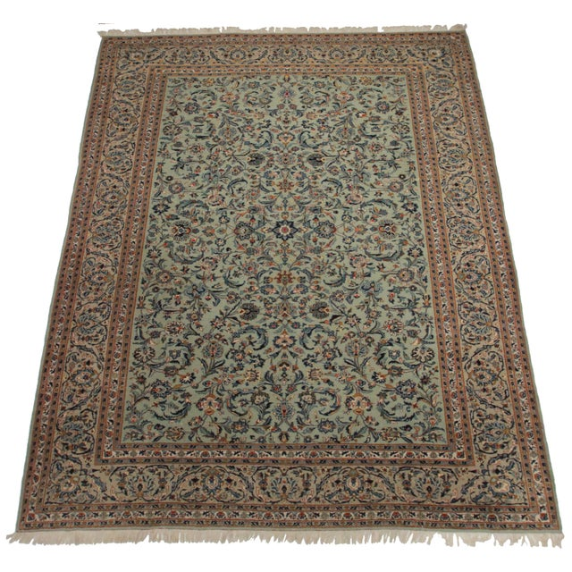 Offered is a Persian Kashan style area rug. The luxurious wool pile features tones of tan, rust, and sage green with an...