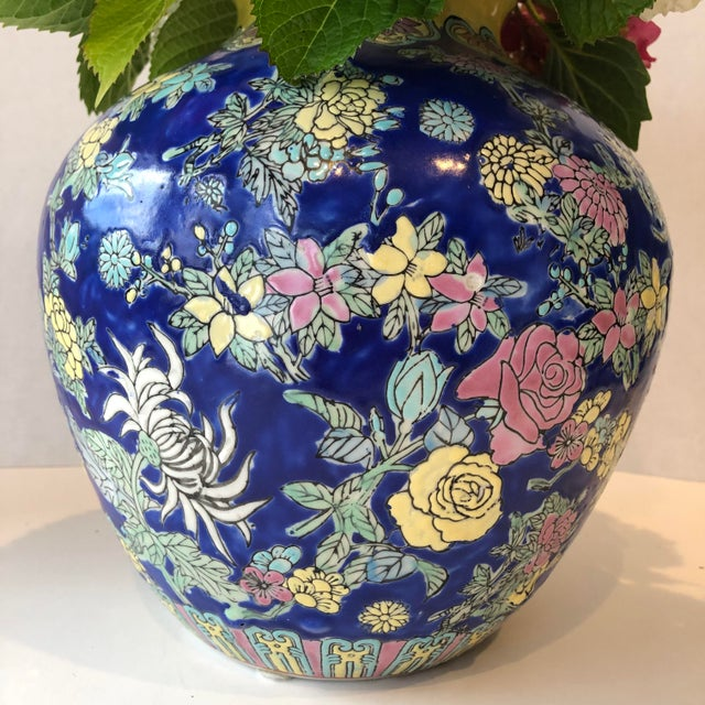 Vintage Chinese ceramic vase with a royal blue background; yellow, pink, white flowers and green/aqua foliage. The floral...