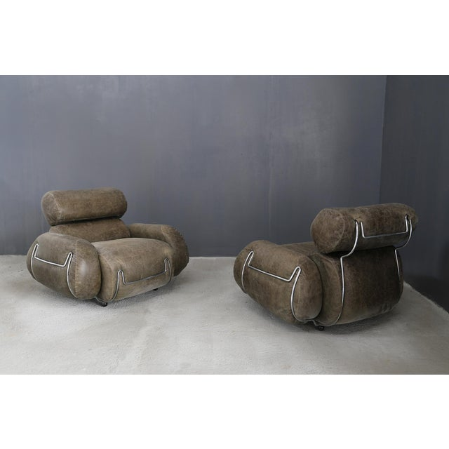 Vintage armchairs in 70's leather and steel. Set of two 70's armchairs in leather and steel. The pair of armchairs are...