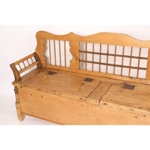 Continental pine settle with two hinged doors on the seat for storage, late 19th century.