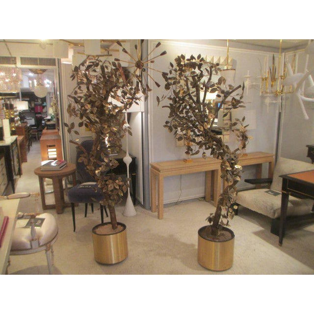 A pair of brass and copper Curtis Jere tree sculptures. Measures: The heights are, H 75 x 31 x 13 H 81 x 31 x 13 Curtis...
