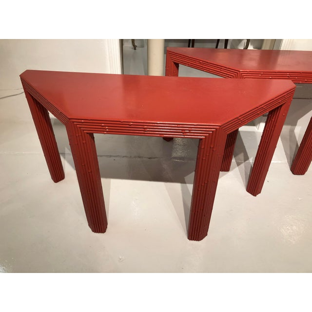 A pair of Chinese style coral red console tables. Each table measures 56 inches at its widest point, 19.5 inches in depth...