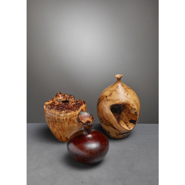 A set of three turned vases from different types of burl wood. The set consists of these pieces: A vase with a very small...