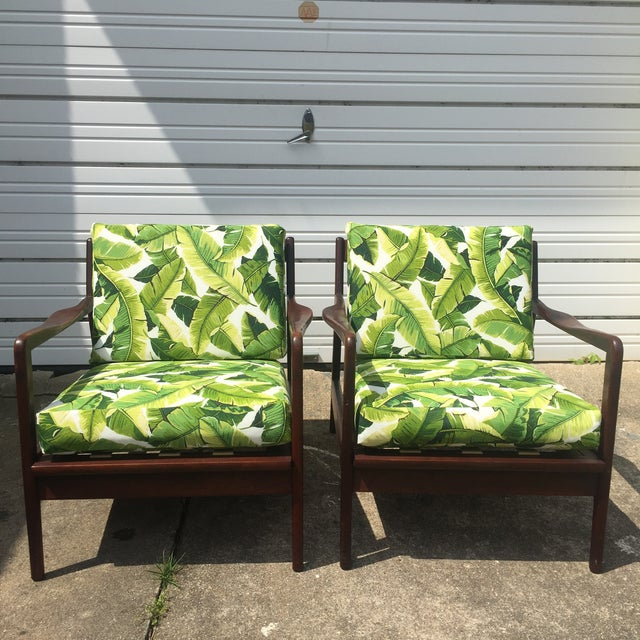 Beautiful pair of walnut lounge chairs with banana leaf upholstery that will bring the tropics to any room. The wood has a...