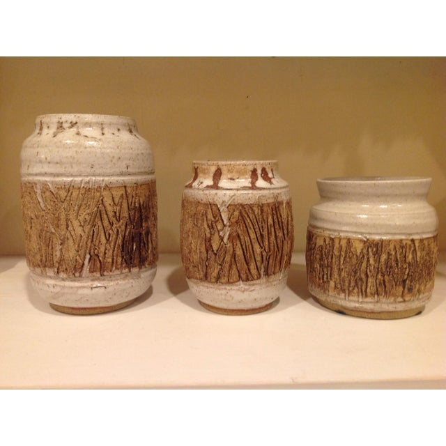 Set of 3 chunky faux box pots in 3 shapes with rustic bark detail on a pale gray stoneware base. Signed Filbin 1980.