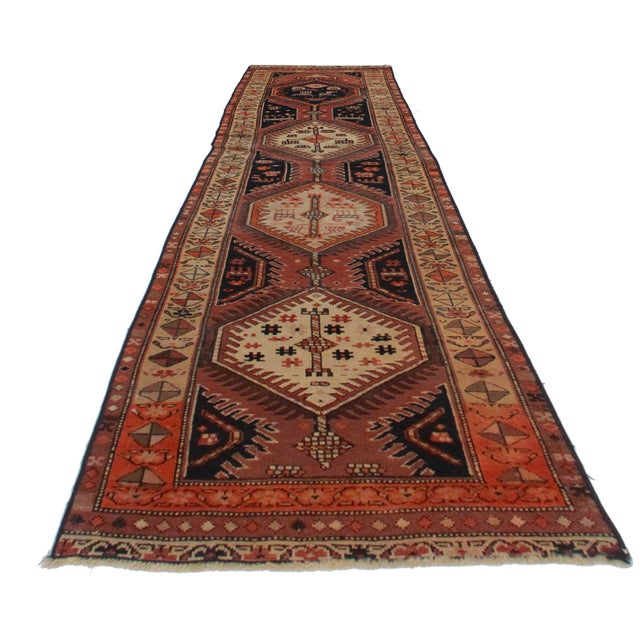 This is a vintage Persian Hamedan runner. Made of hand-knotted wool. Its geometric design features warm earth tones.