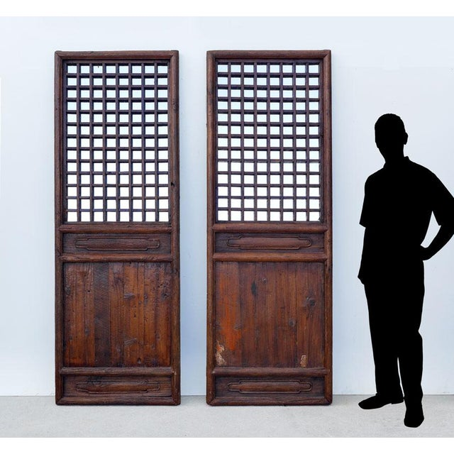 Pair of antique Chinese wood doors. The open square panels of the doors are backed with newer mirrors. Beautiful patina to...