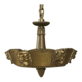 """Early 20th Century American bronze round fixture with 6 """"comedy"""" style faces and a beaded bottom centering a finial For Sale"""
