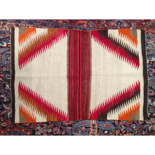 This little Navajo rug was handwoven in the Southwest of the United States in the 1930s and sports electric satin red,...