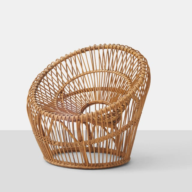A woven wicker lounge chair with concentric circles of support and a cascading front lip. Not marked. Very comfortable.