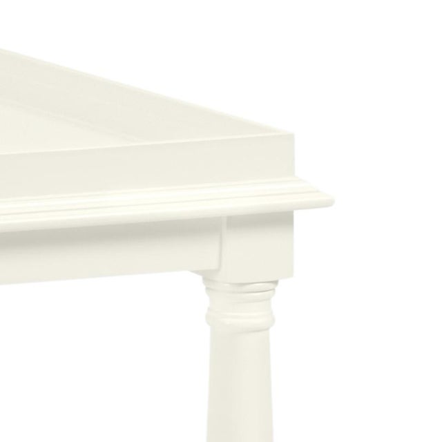 Made of acacia wood, this cocktail table features a gallery shelf and turned legs. Color is Benjamin Moore Cloud White...
