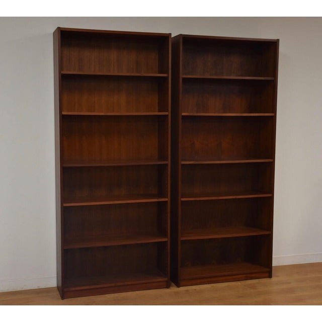A pair of walnut bookcases with ten total adjustable shelves. Minor damage as seen in photos.