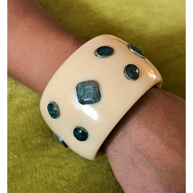 Large cream colored contemporary design Lucite bangle bracelet bezel set with faceted emerald stones. The bangle measures...