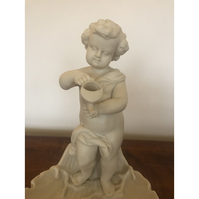 Magical vintage porcelain sculpture of an adorable putti with watering can, perched at the edge of a scalloped shell...