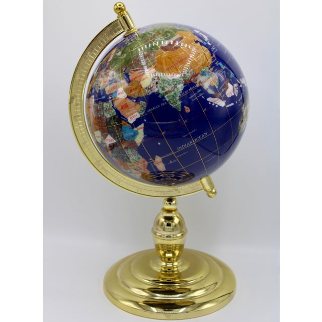 This is a stunning blue lapis globe inlaid with semiprecious gemstones; including turquoise, shell, onyx, jade, and...