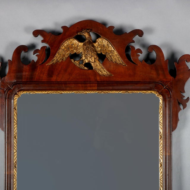 An antique Federal Chippendale wall mirror features cutout scroll form mahogany frame with pierced crest having central...