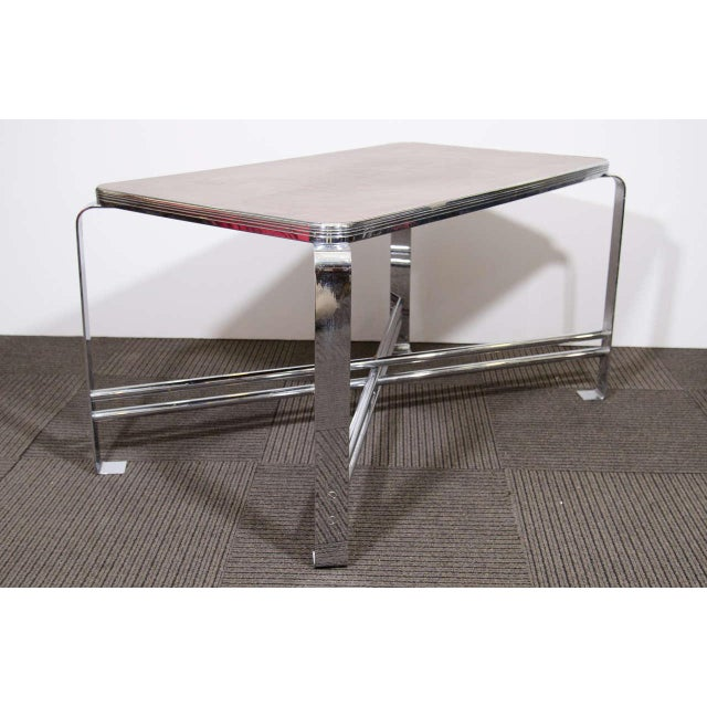 An Art Deco rare Wolfgang Hoffmann coffee table with flat band chrome over brass and wood veneer bakelite laminate top.