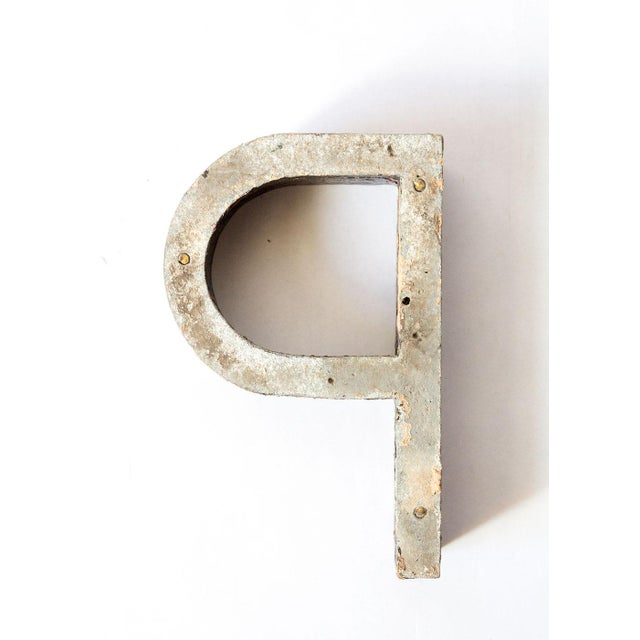 Beautifully aged metal letter P. Black chippy paint shows a pop of muted pink underneath.