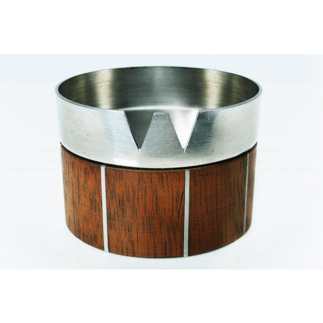 A fabulous ashtray in walnut with inlaid pewter detail and a brushed steel top. Probably a collabortive design by Paul...