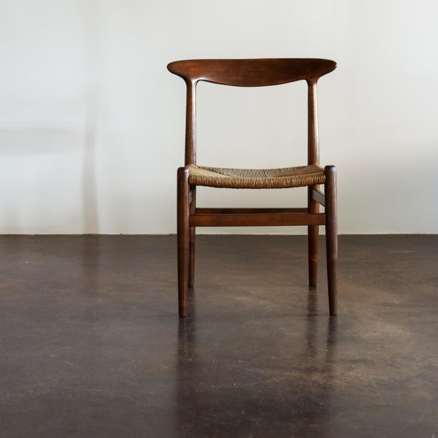Four W2 dining chairs in oak with papercord seats by Hans Wegner. In excellent vintage condition, Denmark, 1950s.