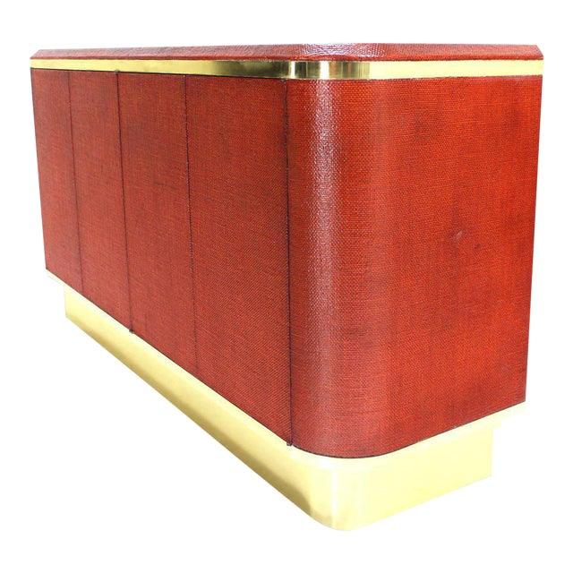 Brick red color grass cloth with brass trim mid-century modern credenza possibly designed by Karl Springer. Made in the...