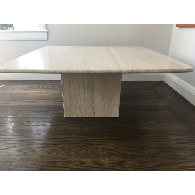 This Italian travertine coffee table has a separate square base that supports a top with gently curved corners and a bull-...