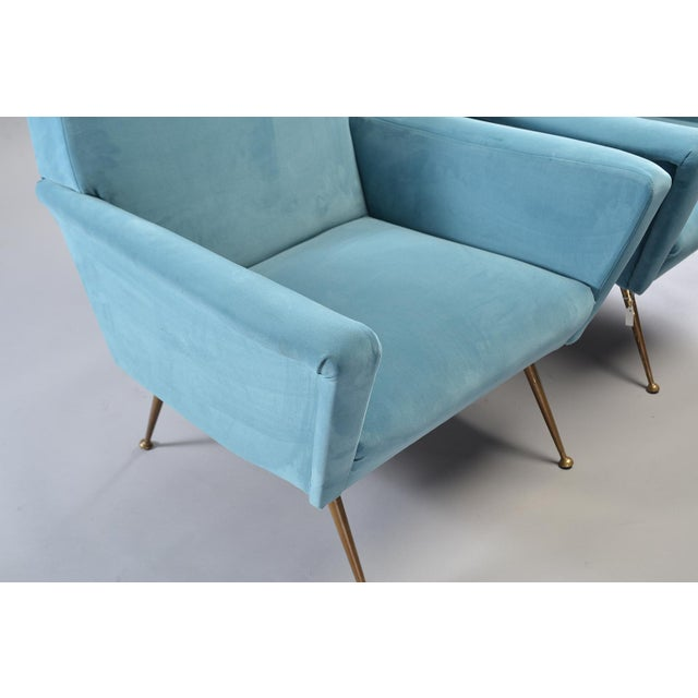 Pair of Italian mid century arm chairs with great lines, flared boxy arms and slender gold tone metal legs. Newly...