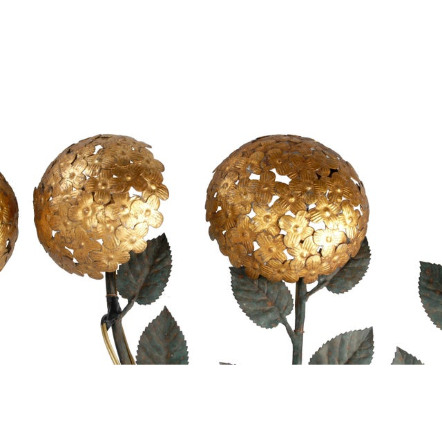 Pair of Italian florentine brass and iron wall sconces with floral design. Wired for Europe and uses each three light...