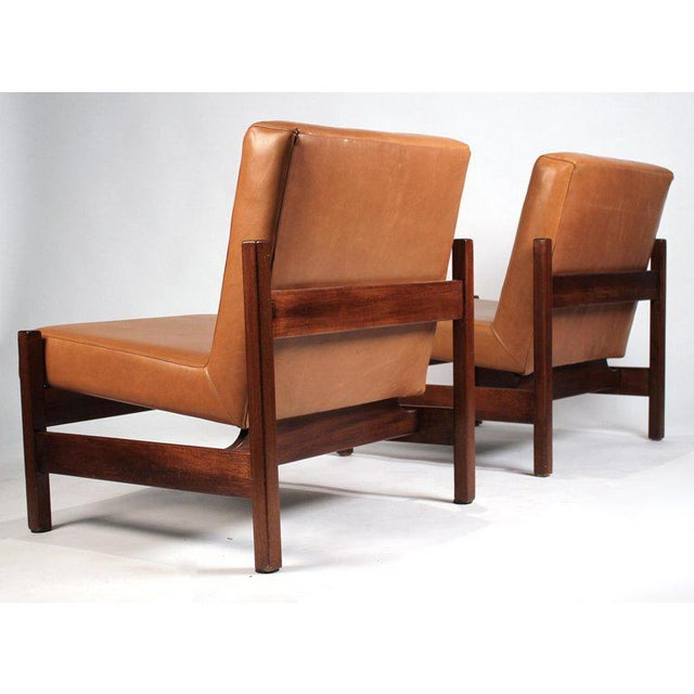 A pair of Peroba wood chairs upholstered in a rich caramel leather. Forma distributed and produced many designs by Knoll...