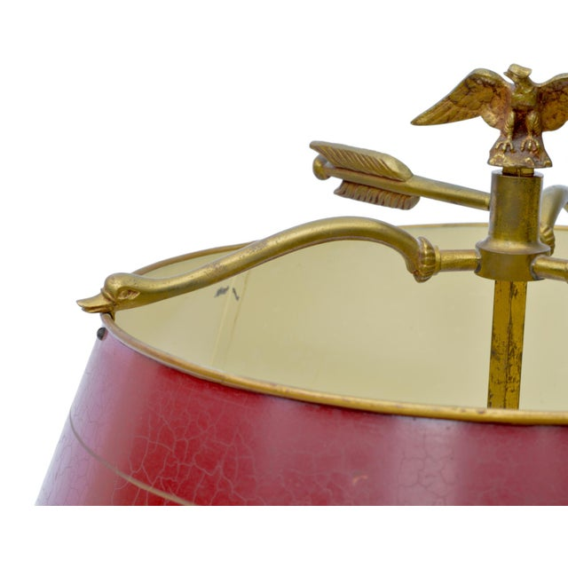 A classic Bouillotte lamp having wonderful French Empire stylings. The deep red tole' painted shade perches atop a...