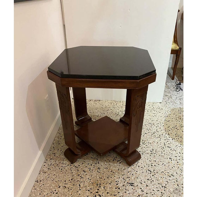 This stylish American Art Deco table is detailed with hand carved stylized flowers and leaves and it was acquired from a...
