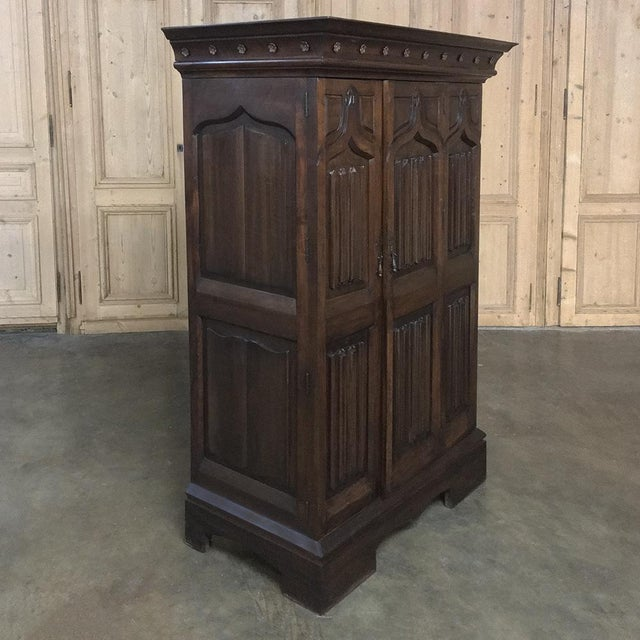 This handsome 19th Century French Gothic Solid Walnut Armoire ~ Bonnetiere was created from fine French Walnut, and...