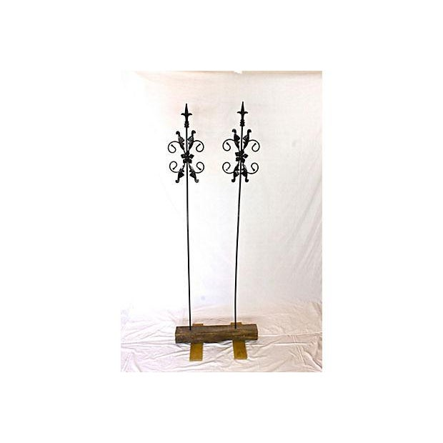 Set of two iron garden stakes painted in black. These stakes come with a handmade wooden base. No maker's mark.