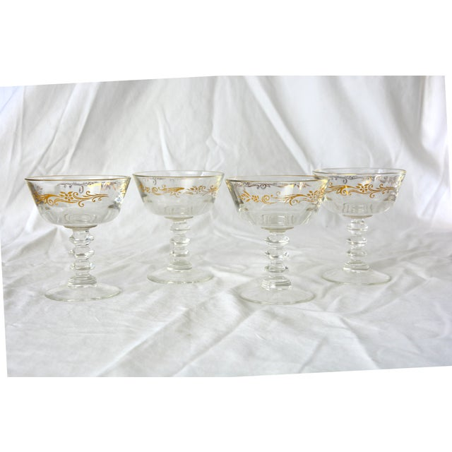 A stunning set of four goblets adorned with metallic gold filigree.