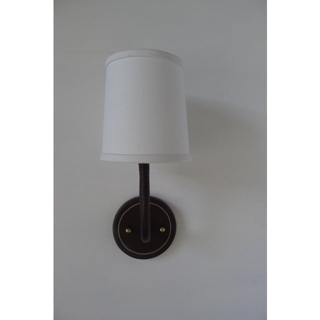 Paul Marra Leather Wrapped Adnet inspired wall sconce, shown in brown, with top-stitched detailing. Top-stitching detail...
